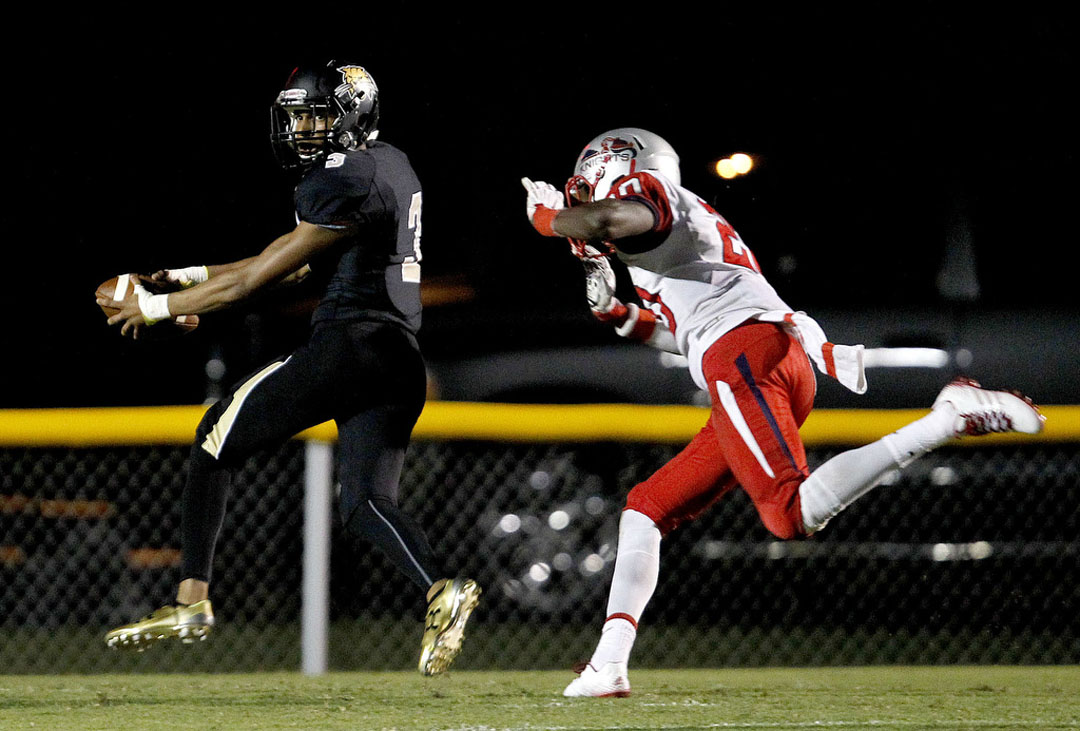 Buchholz Bobcats receiver Barry Moore runs for a touchdown past Vanguard Knights defender Blake Johnson on Friday, Sept. 25, 2015 in Gainesville, Fla. Buchholz defeated Vanguard 33-32. Matt Stamey/Staff photographer
