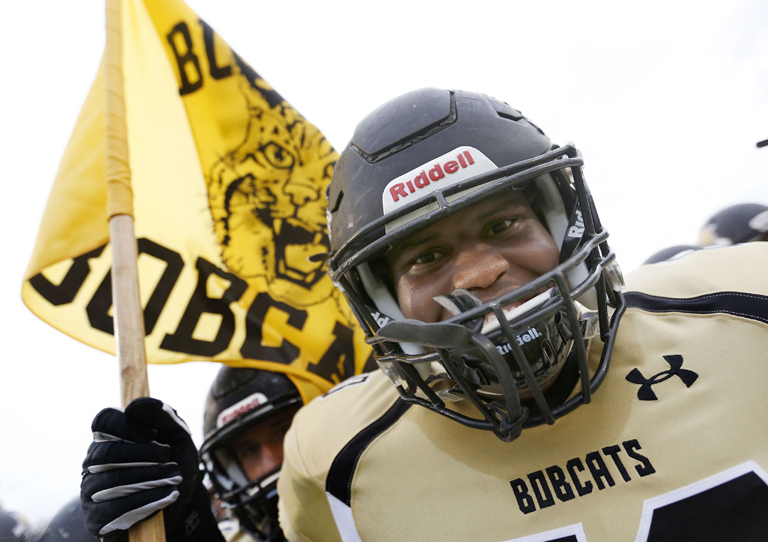 Buchholz Bobcats offensive lineman Darius Wilson yells and holds the team flag before taking the field against the Eastside Rams on Friday, August 28, 2015 in Gainesville, Fla. Buchholz defeated Eastside 48-13. (Matt Stamey/Staff photographer)