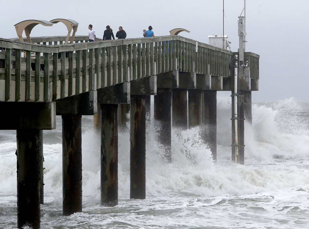People stand on the pier as waves crash below as Hurricane Matthew approaches on Thursday, Oct. 6, 2016 in St. Augustine, FL. Matt Stamey/Gainesville Sun