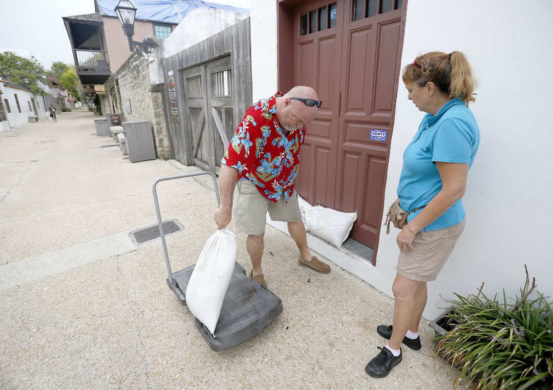 Gary Easton and his wife Michelle Easton work to place sandbags at the door of Fudge Buckets, their store on St. George Street, as Hurricane Matthew approaches on Thursday, Oct. 6, 2016 in St. Augustine, FL. Matt Stamey/Gainesville Sun