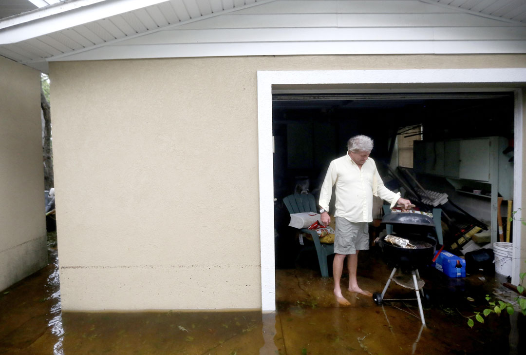 Kelly Bland grills a brisket while standing in floodwaters outside his garage during Hurricane Matthew on Thursday, Oct. 6, 2016 in St. Augustine, FL. Bland rode out the storm at his house just off A1A. Matt Stamey/Gainesville Sun