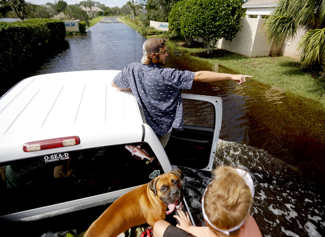 Kyler Williams points while riding through flooded streets of the Seagate neighborhood while driving around to see damage on the island after Hurricane Matthew on Friday, Oct. 8, 2016 in St. Augustine, FL. Matt Stamey/Gainesville Sun