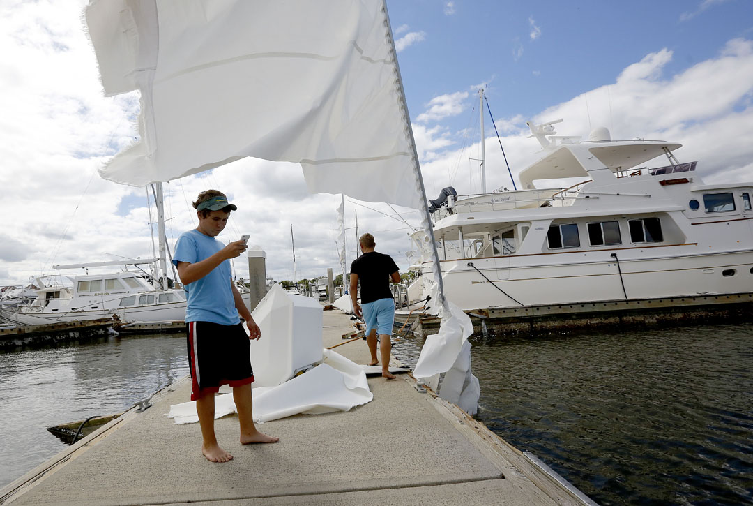 While standing under a sail, Walker Daivs takes a video of the sunken boat at the Conch Marina after Hurricane Matthew on Friday, Oct. 8, 2016 in St. Augustine, FL. Davis details boats for many of the owners and came to the maria to check on the vessels. Matt Stamey/Gainesville Sun