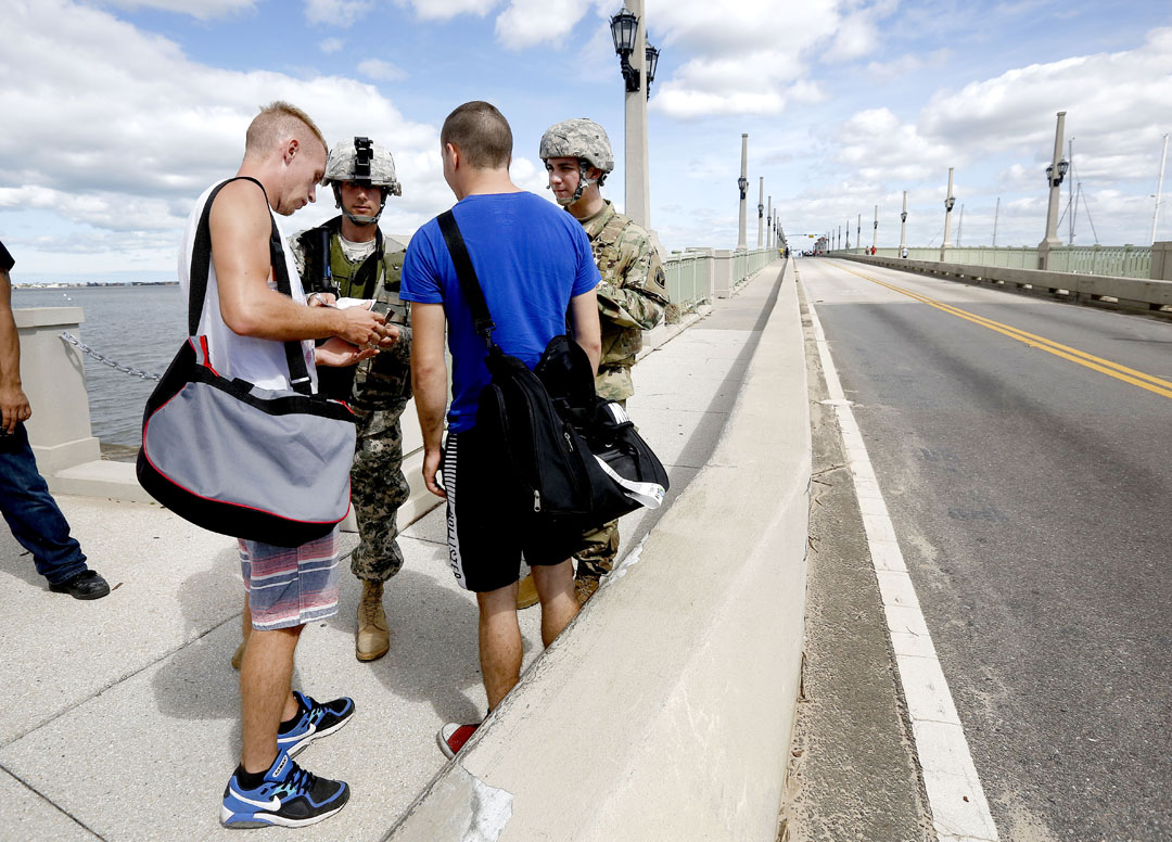 Florida National Guard members check identification at the base of the Bridge of Lions after Hurricane Matthew on Friday, Oct. 8, 2016 in St. Augustine, FL. Only residents of the island were able to walk across. Vehicle traffic was not allowed to cross. Matt Stamey/Gainesville Sun