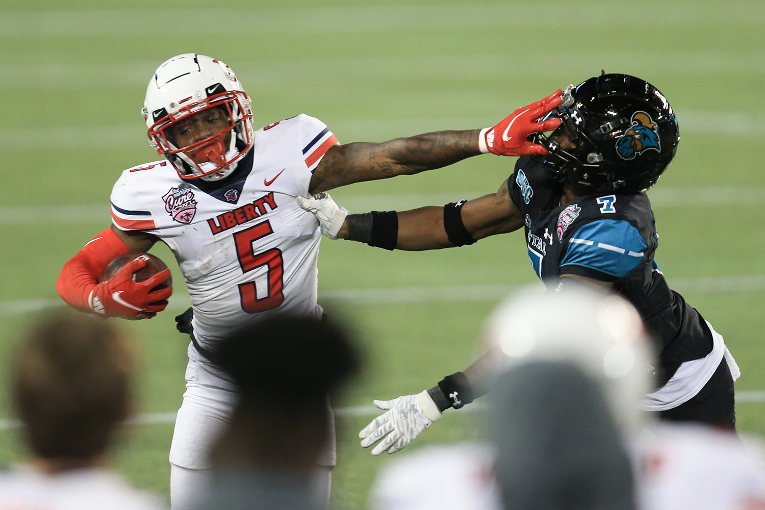 Liberty wide receiver DJ Stubbs (5) stiff arms Coastal Carolina cornerback D'Jordan Strong (7) during the second half of the Cure Bowl NCAA college football game Saturday, Dec. 26, 2020, in Orlando, Fla. (AP Photo/Matt Stamey)